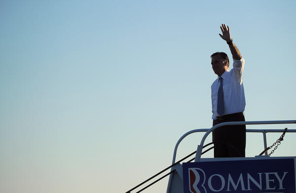 Mitt Romney waves to supporters while boarding his campaign plane in Coraopolis, Pa.