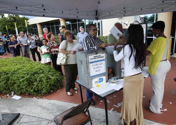 Voters line up to turn in their absentee ballots in person at the Miami-Dade County Elections Department, in Doral, Fla.