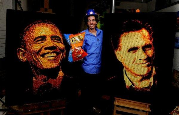 Artist Jason Baalman poses in front of portraits of President Obama and GOP challenger Mitt Romney that were made entirely of more than 2,000 individual Cheetos snacks.