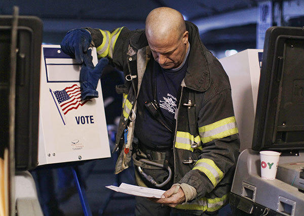A firefighter votes in a tent that is being used as a polling place in Rockaway, Queens as New York recovers from Hurricane Sandy on November 6, 2012. The aftermath of the natural disaster made Tuesday's presidential election a voting obstacle course, with dozens of polling stations in New Jersey and New York forced to relocate because of storm damage.