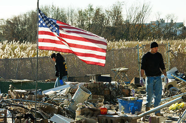 Friends and members of the Puglia family sift through the remains of their missing home for valuables on November 6, 2012 after Hurricane Sandy hit the coastal estuary(to the rear) in the Oakwood Beach area of  Staten Island, New York.