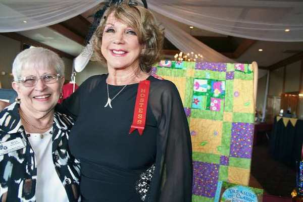 Posing in front of a Judy Gorham crafted quilt in the Patrons Club silent auction, are, from left, Glendale resident Rita Even and Ginny Bundick.
