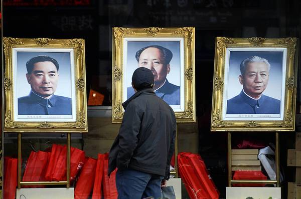 Portraits of late Chinese leaders Chou En-lai, from left, Mao Tse-tung and Liu Shaoqi attract the attention of a passerby in Beijing. China's Communist Party will be announcing its next leaders at its weeklong congress.