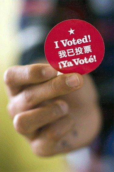 "A man holds an ""I voted"" sticker after casting his ballot at a polling station in San Francisco."