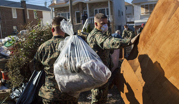 Marines from the 26th Marine Expeditionary Unit and U.S. Navy seamen offer assistance to local residents removing household items damaged by Superstorm Sandy on Staten Island, N.Y.
