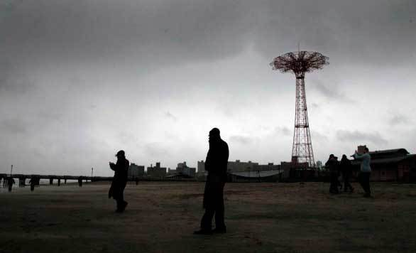 People brave high winds and blowing sand along Coney Island beach in Brooklyn as Hurricane Sandy approaches New York.