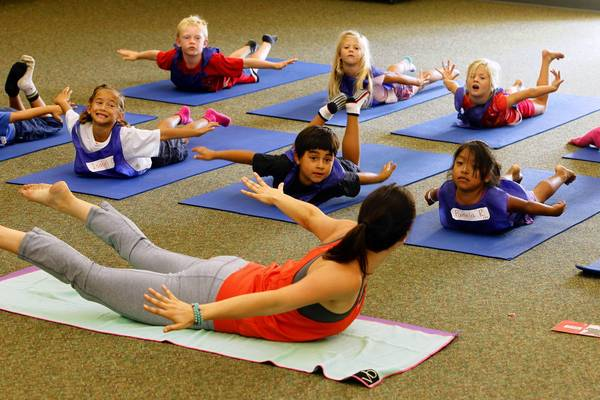 Yoga teacher Jackie Bergeron works with students at Paul Ecke Central Elementary School in Encinitas. Students attend two 40-minute yoga classes each week.