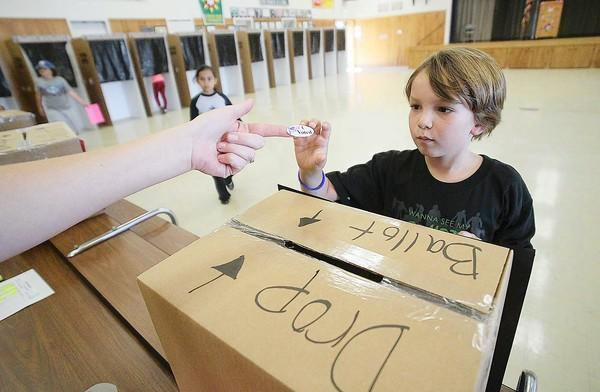 Everest Withers, 9, gets an I Voted sticker after he cast his ballot during the Davis Magnet School's student council elections on Tuesday.