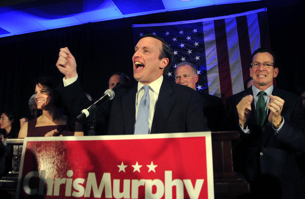 Chris Murphy acknowledges the crowd assembled in the Hartford Hilton ballroom after beating Linda McMahon for the U.S. Senate. His wife Cathy Holahan is at left and Gov. Dannel Malloy is to his right.