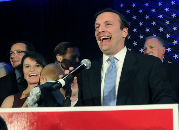 Chris Murphy acknowledges the crowd assembled in the Hartford Hilton ballroom after beating Linda McMahon for the U.S. Senate. His wife Cathy Holahan is at left holding their son, Rider. At far right is Gov. Dannel Malloy.