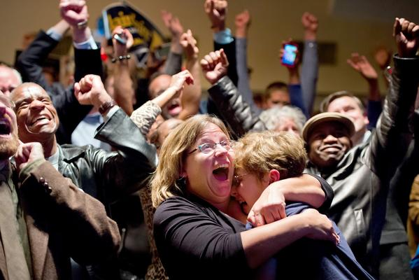Michelle Zielinski, center, hugs Jared Goudsmit after President Obama is projected to win during an election watch party at the Chase Park Plaza Hotel in St. Louis, Mo.
