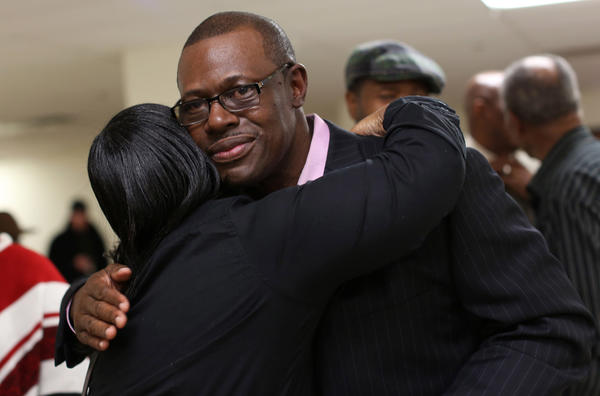 Indicted former state Rep. Derrick Smith, who represented the 10th district, is hugged by a supporter in his small election night party after the numbers favored him in his race against Lance Tyson.