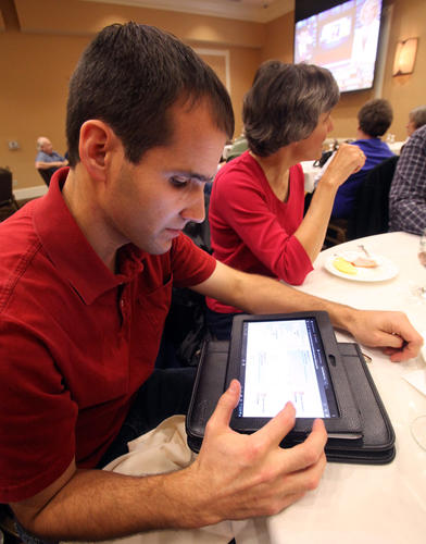 David Novstrup, republican candidate for District 3 State House of Representatives, uses a tablet to check election results Tuesday night at the Dakota Event Center. photo by john davis taken 11/6/2012
