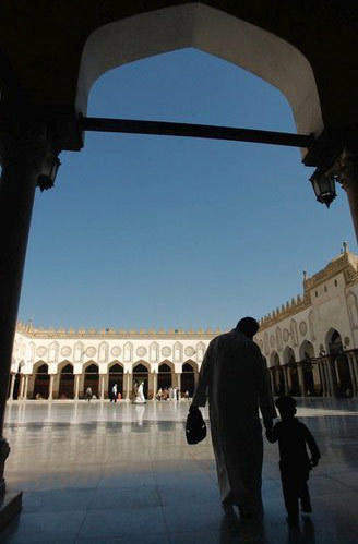 A father and son walk to prayer through a courtyard at the thousand-year-old mosque of Al-Azhar.