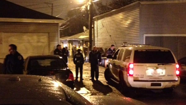 Police near an alley where a body was found in a burning trash bin on Nov. 6.