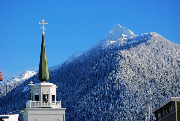 The mountains that dominate the landscape of Sitka, Alaska, form a majestic backdrop for the bell tower of St. Michael's Cathedral, the remote town's place of worship for members of the Russian Orthodox faith.