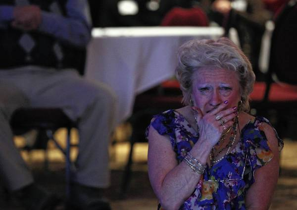 A woman weeps Tuesday after Fox News declares President Barack Obama the winner in the 2012 election at a Republican party at the Holiday Inn Express in Janesville, Wis.