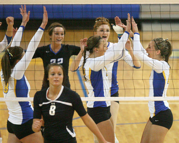 Aberdeen Central's Amanda Tobin, far right, celebrates a kill to win the first game with teammates Brianna Kusler, center, Lauren McCafferty, back center, Meggie Hanson (32) and Caitlin Rasmusson, far left, during Tuesday night's District 3AA championship match at the Golden Eagles Arena. In the foreground is Mitchell's Kerri Young (8).