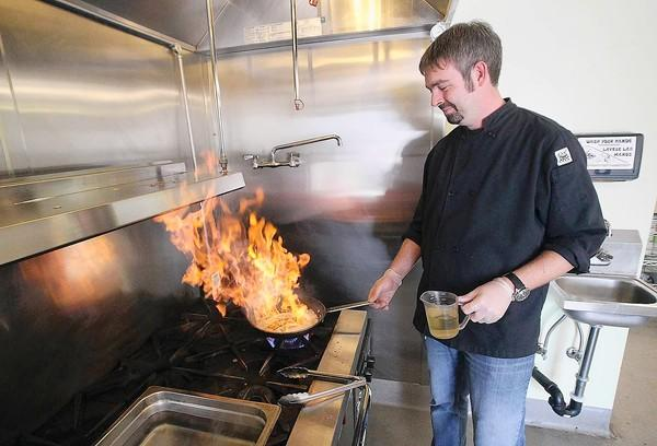 Nick Samons, the executive chef at Fit Foods 4 Life, cooks fresh, wild salmon on Tuesday.