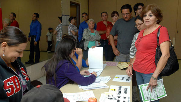 Poll workers help a long line of voters as the poll precincts were nearing to closing hours at Calexico Community Center on Tuesday evening. Two precincts were at the center.