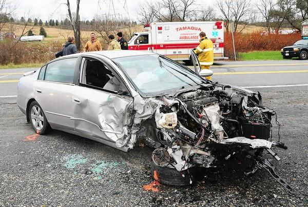 A mangled car sits along Route 309, just south of Tamaqua, on Monday afternoon after it collided with a tractor-trailer, injuring a woman and a 4-year-old child.