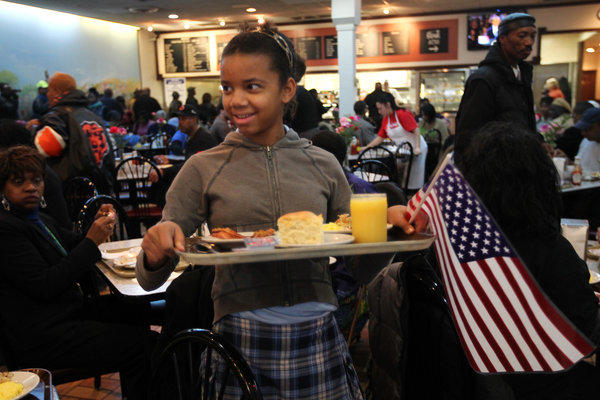 Sydney Green, 11, carries a flag with her breakfast at Valois restaurant in President Obama's neighborhood.