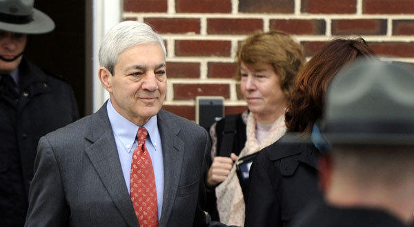 Former Penn State president Graham Spanier, center, leaves his arraignment in Harrisburg, Penn.