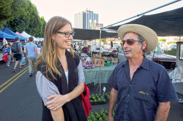 Sarah Delevan of the Produce Project, which resells farmers market produce at other sites, chats with farmer Alex Weiser.