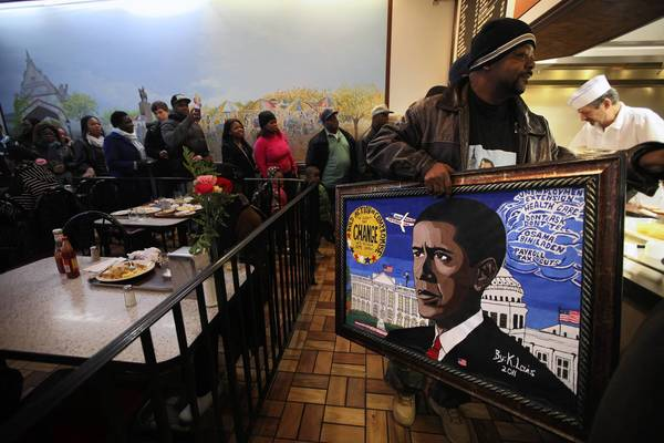 Kevin Lewis carries one of his paintings while getting breakfast at Valois Cafeteria.
