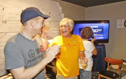 Volunteer Nicholas Hernandez, middle, celebrates with others at the Democratic Party headquarters in Laguna Beach after President Barack Obama was reelected Tuesday night.