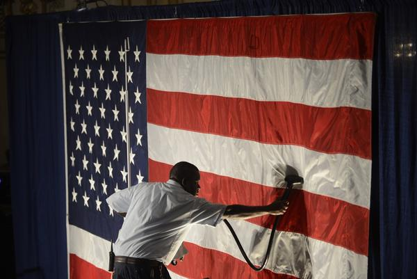 Hotel employee Denzil Telphia, of Boston steams the wrinkles from an American flag hanging as a backdrop at Elizabeth Warren's election night party  in Boston, Massachusetts, November 6, 2012.