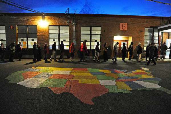 ALEXANDRIA, VA - NOVEMBER 06: People enter Washington Mill Elementary School to cast their vote in the U.S. presidential race, on November 6, 2012, in Alexandria, Virginia. Recent polls show that U.S. President Barack Obama and Republican presidential candidate Mitt Romney are in a tight race.