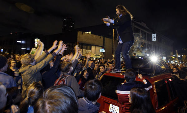 A man stands on a car and encourages a crowd gathered to celebrate the election results in Seattle's Capitol Hill.