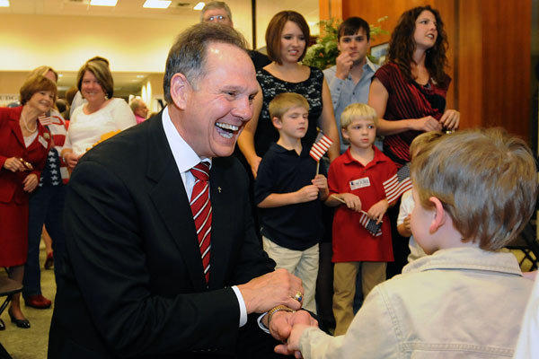 Roy Moore greets Adam DuPre', 3, of Pike Road, Ala., at his election party in Montgomery, Ala.