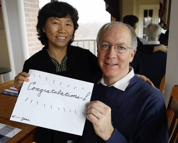 Democrat Bill Foster, candidate-elect for the 11th Congressional District, and his wife Aesook Byon show a handwritten sign put on the door of their Naperville home by neighbors last night. Foster defeated Republican Judy Biggert.