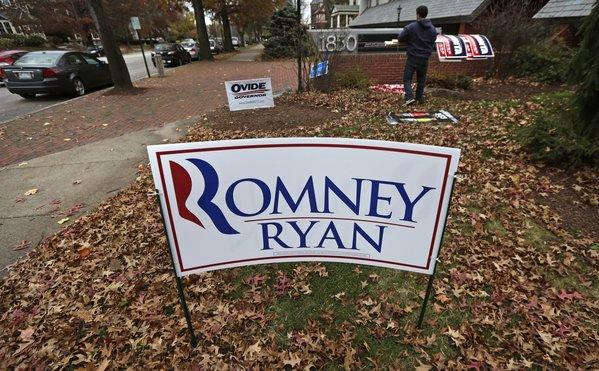 A campaign worker removes candidate signs from in front of Mitt Romney's campaign office in Manchester, N.H.