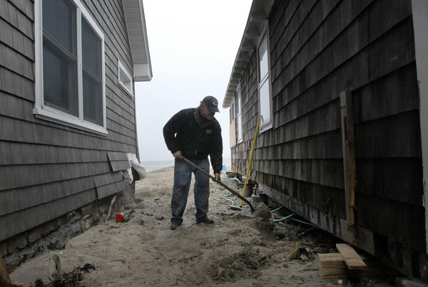 Paul Tinks, of Harwinton, shovels sand into the foundation of his home on Hawks Nest Beach in Old Lyme to protect the pipes from freezing. Trinks had just worked with a plumber to shut off the water to his rental home, which was knocked off its foundation by storm Sandy. People in the area were preparing for Nor'easter Athena which was heading into the area.