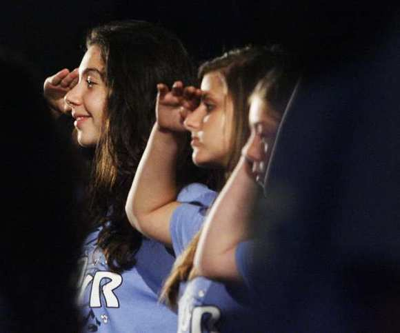 Rouzanna Asatryan, 13, smiles as she salutes at the conclusion of a chorus of military anthems at Wilson Middle School at a Veteran's Day assembly on Wednesday, November 7, 2012.