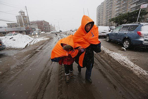 Fatima Quentiro walks with her granddaughter Galalea Castro through the snow to a bus stop in the Rockaway neighborhood of New York City's Queens borough. They are wearing jackets donated by the NYC Marathon.