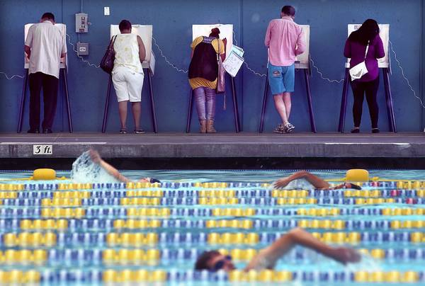 Voters cast their ballots as others swim laps at a pool in Echo Park on Tuesday.