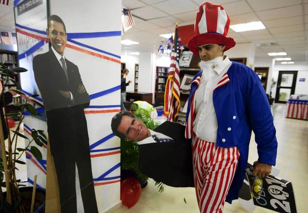 "In Jerusalem, a U.S. citizen dressed as Uncle Sam removes a cardboard figure of Mitt Romney after the GOP challenger's defeat. One analyst said that President Obama's reelection was greeted with ""a sense of relief in the Middle East."""