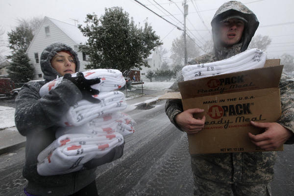 Volunteer Karina Ayubi and National Guardsman Brandon Kyle distribute blankets donated by the American Red Cross to residents without power in the wake of Superstorm Sandy in Little Ferry, N.J.