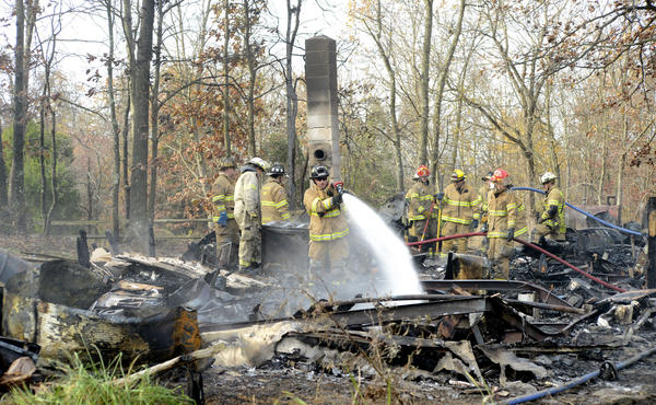 Firefighters are shown Monday working through the burned mobile home at 1807 Back Road near Sharpsburg.