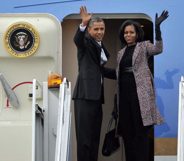 President Barack Obama and first lady Michelle Obama wave while boarding Air Force One before leaving O'Hare International Airport in Chicago, Ill.