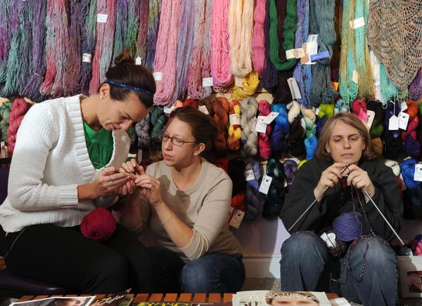 Ashley Creel, of Little Italy, follows crochet directions from Melissa MacMichael, of Hampden, while Caitlin Cross-Barnet, of Tuscany-Canterbury, knits at Lovelyarns in Hampden.