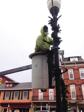 Borough of Waynesboro (Pa.) employee Chris Eyler hangs garland on a street lamp Wednesday on East Main Street. The borough is gearing up for a string of holiday activities later this month, including a tree lighting on Nov. 16 and the Christmas parade on Nov. 17.