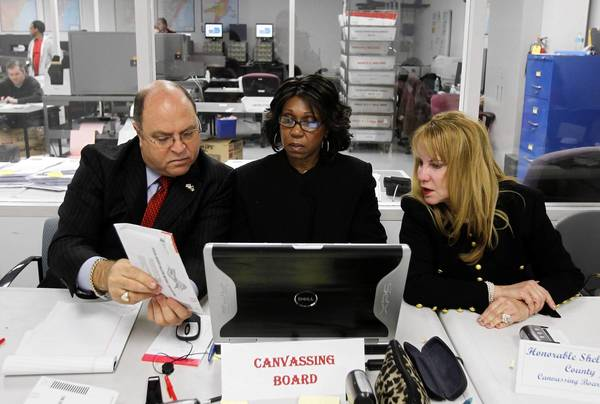 Miami-Dade County Judges Andrew S. Hague, left, and Shelley J. Kravitz, right, check absentee ballots as clerk Jean Horne looks on in Doral, Fla. State election officials expect to know the outcome in the presidential contest by Saturday.