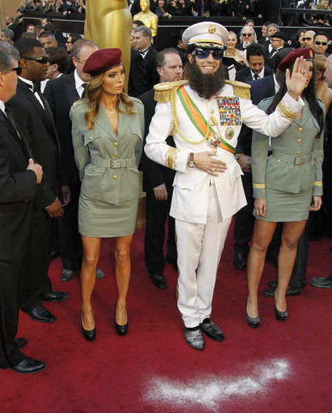 "Sacha Baron Cohen's Adm. Gen. Shabazz Aladeen not only made his way onto the Oscars red carpet in February 2012; the character also made his way over to Ryan Seacrest and managed to stun the usually unflappable host -- showering the diminutive Seacrest with the ""ashes"" of the late North Korean dictator Kim Jong Il."