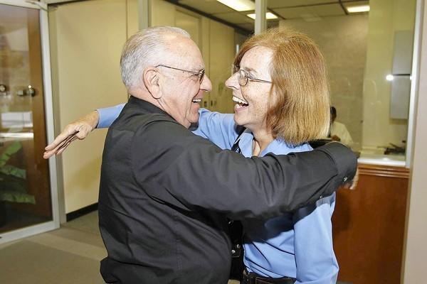 Newly elected City Councilwoman Sandy Genis, right, shares a hug with Interim Fire Chief Tom Arnold as she tours City Hall and introduces herself to city employees Wednesday.