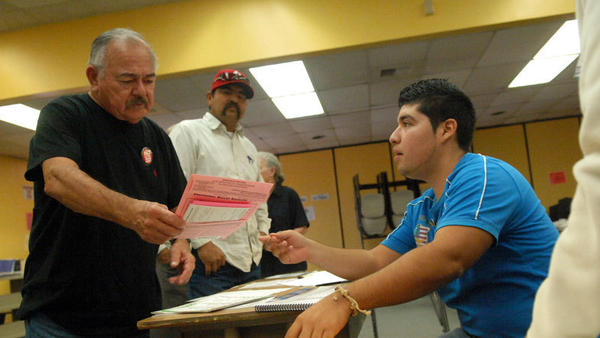 FROM RIGHT: Poll volunteer Cesar Flores helps Emilio U. Garcia with a provisional ballot envelope Tuesday at the polling place at Mains Elementary School in Calexico on Tuesday.